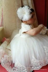 fetita in rochita alba de mireasa cu trena delicata de dantela